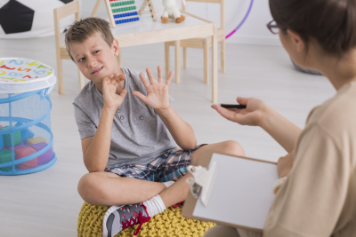 Little stubborn boy with behavioral problems refusing to work with female therapist