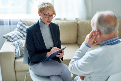 female psychologist taking to senior man during consultation